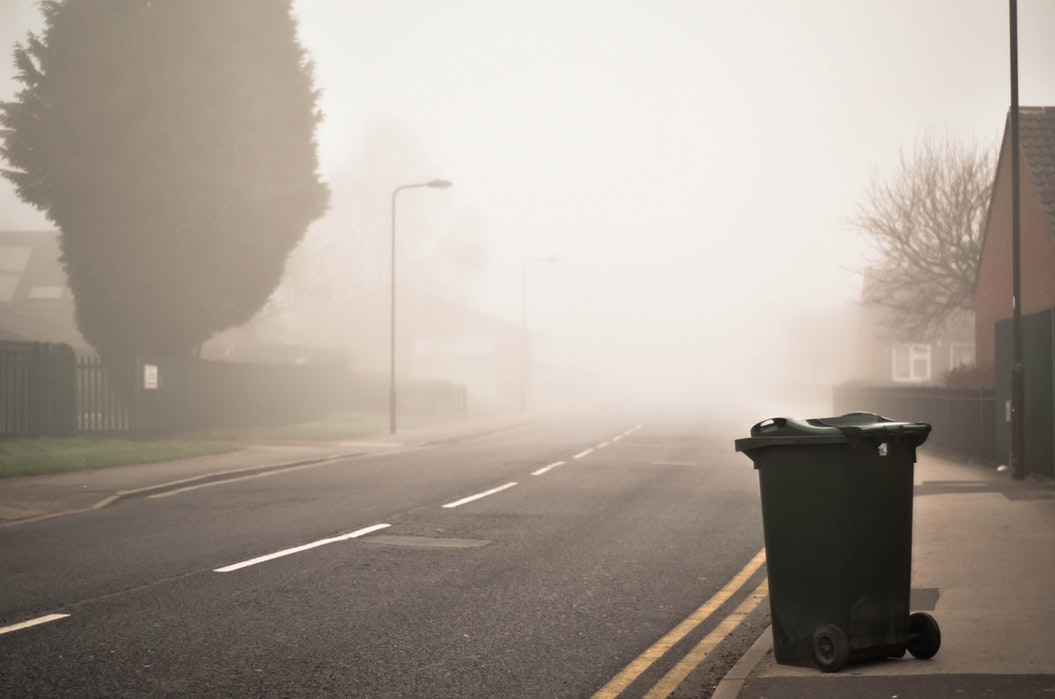 A garbage can sits by a road with fog in the background.