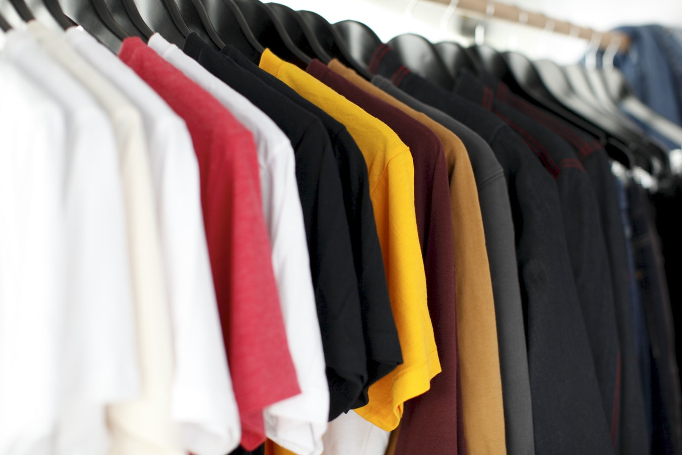 Clothing of various colours hangs on a rack.